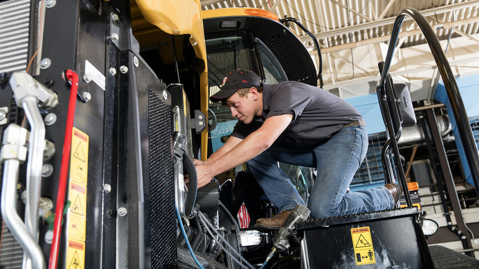 Devon Vancura, a senior agricultural engineering major, checks a connection for a testing monitor in the Nebraska Tractor Test Laboratory. The facility is the designated tractor testing station for the entire United States.