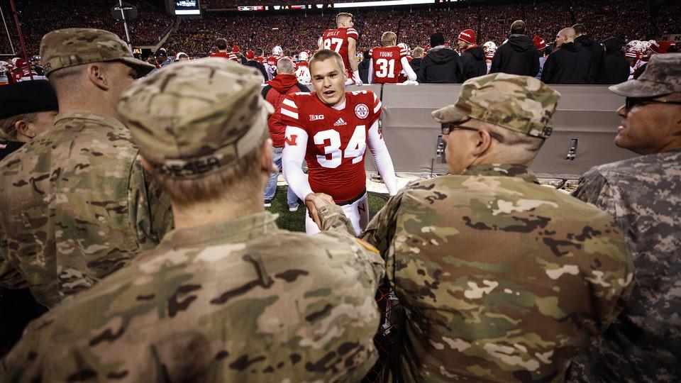 Husker kicker Drew Brown shakes hands with veterans during the 2016 football game against Minnesota in Memorial Stadium.