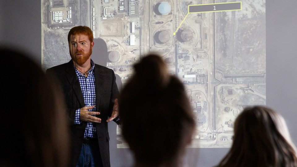 Tyler White teaches while illuminated by a large satellite image of an Iranian oil refinery. White, interim director of the National Security Studies program, recently earned the International Association for Intelligence Education's Instructor of the Year award.
