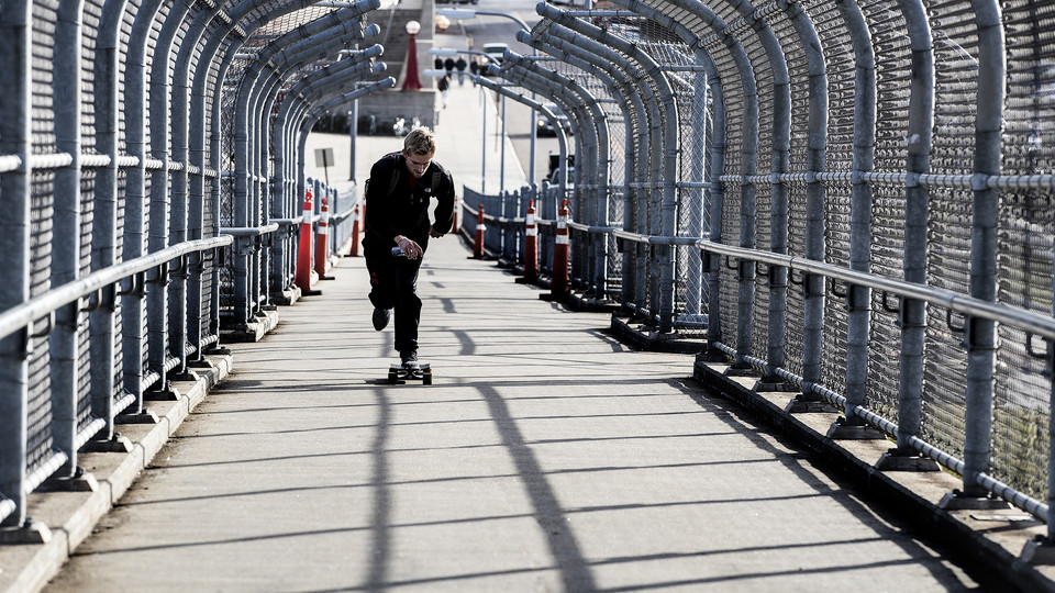 A skateboarder accelerates up the 10th Street pedestrian bridge. The walkway will be closed for a maintenance project on Feb. 20.