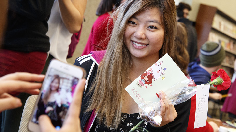 Caitlin Dinh displays her chocolates and Valentine's Day gifts Feb. 14 as her friend takes her photo in the Kawasaki Reading Room.