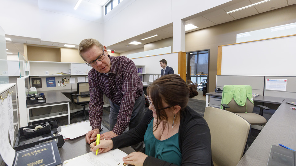 Professor Kevin Ruser and third-year law student Kelsey Heino review a case in the new workspaces of the Marvin and Virginia Schmid Clinic Building. Professor Ryan Sullivan is in the background.