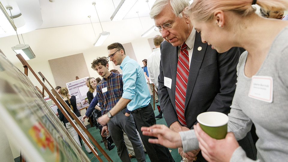 Catherine Berrick (right) explains her research on bats to Nebraska Sen. Robert Hilkemann during the 2017 Spring Research Fair breakfast and poster presentation at the State Capitol building. Students will interact with senators as part of the 2018 fair on April 10.
