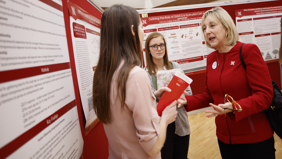 Donde Plowman, executive vice chancellor and chief academic officer, discusses a research project with students during the 2017 Spring Research Fair.