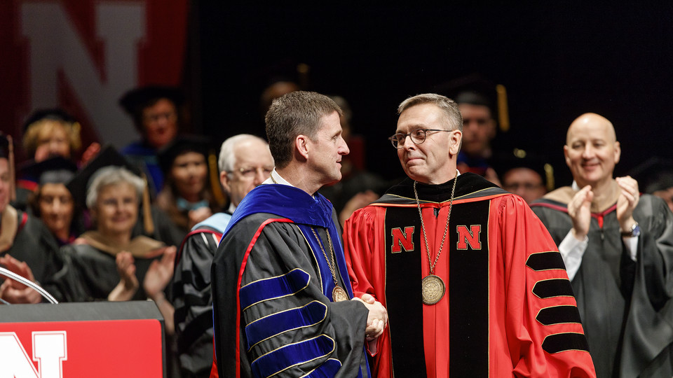 Hank Bounds (left), president of the University of Nebraska system, congratulates Chancellor Ronnie Green after officially installing Green as Nebraska's 20th chancellor. Gov. Pete Ricketts applauds in the background.