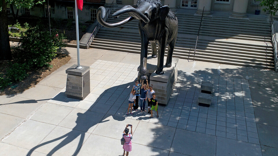 NU State Museum visitors pose for a photo with Archie outside of Morrill Hall.