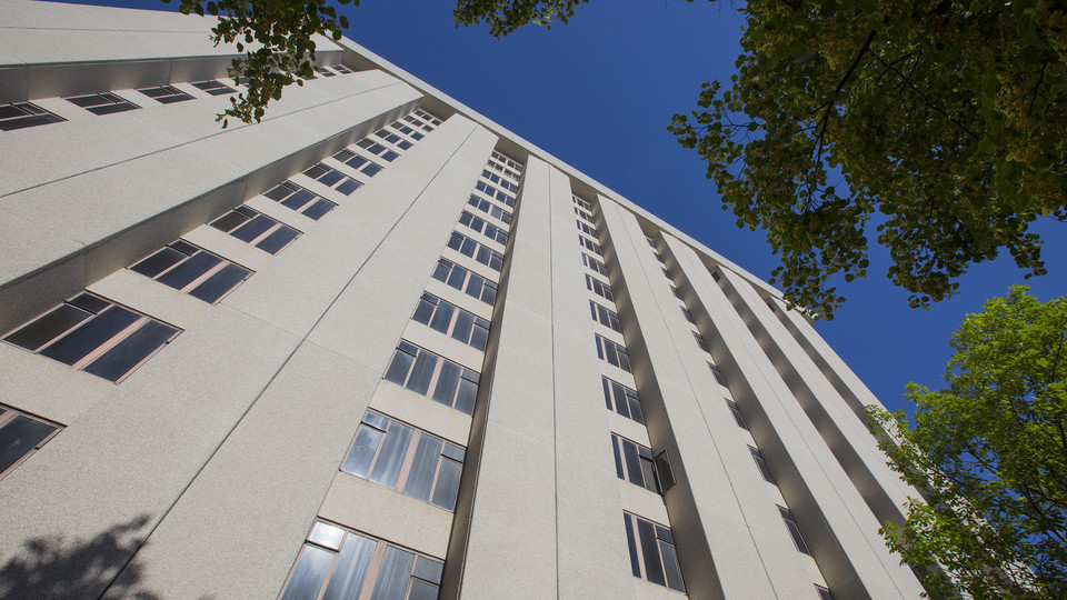 The 13 floors of Cather Hall stretch upward along 17th Street at the University of Nebraska–Lincoln. Both Cather and Pound halls as well as the dining complex between the two towers are being demolished.