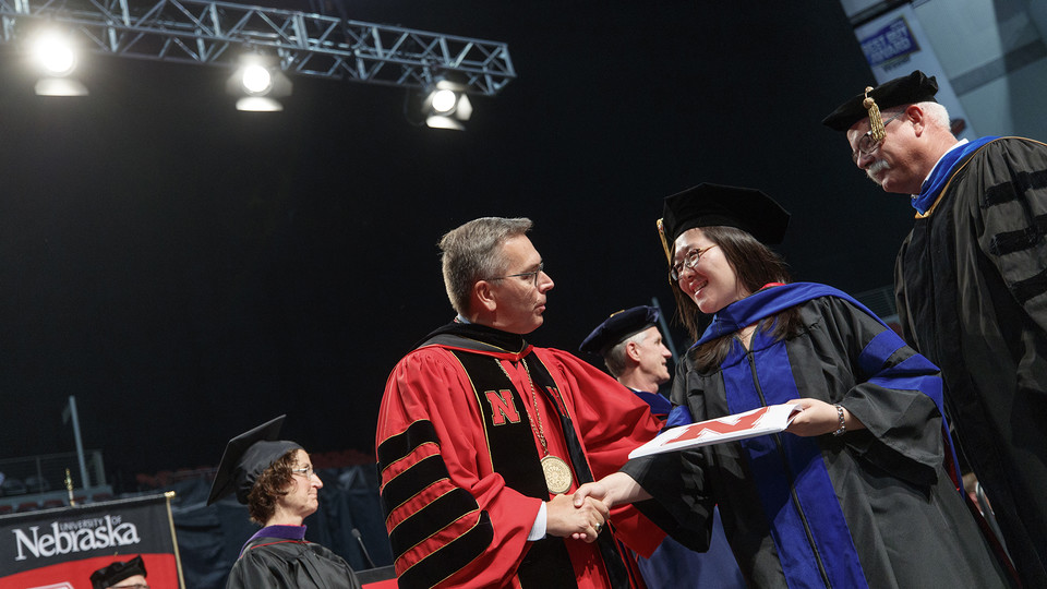 Chancellor Ronnie Green shakes hands with a graduate during summer commencement exercises. Nearly 700 degrees were awarded on Aug. 12.