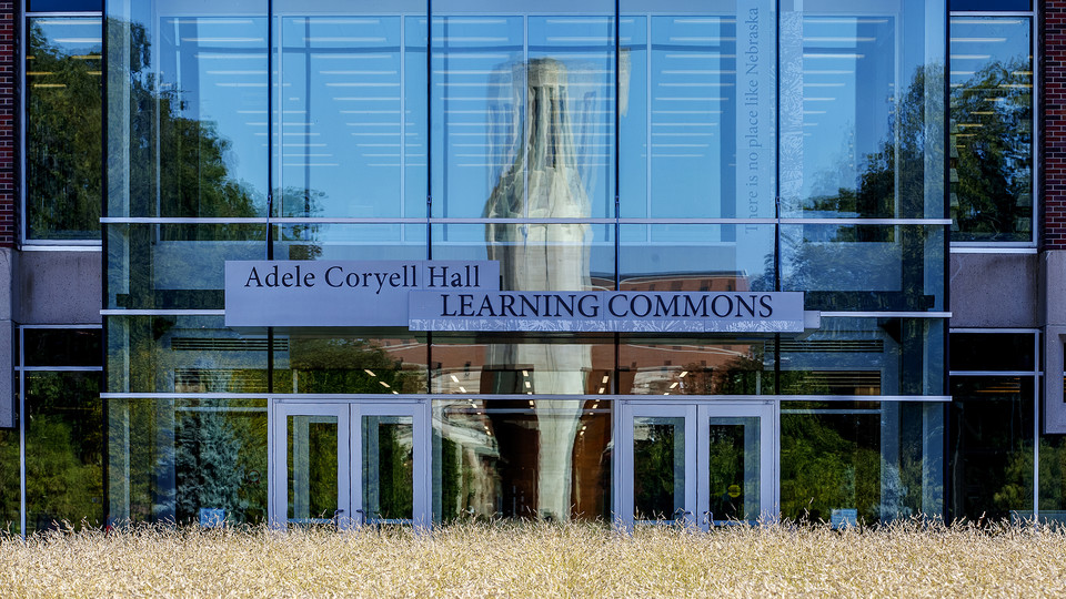 A reflection of the Green Point sculpture, Mueller Tower and Coliseum are distorted by the windows on the north side of the Adele Hall Learning Commons.