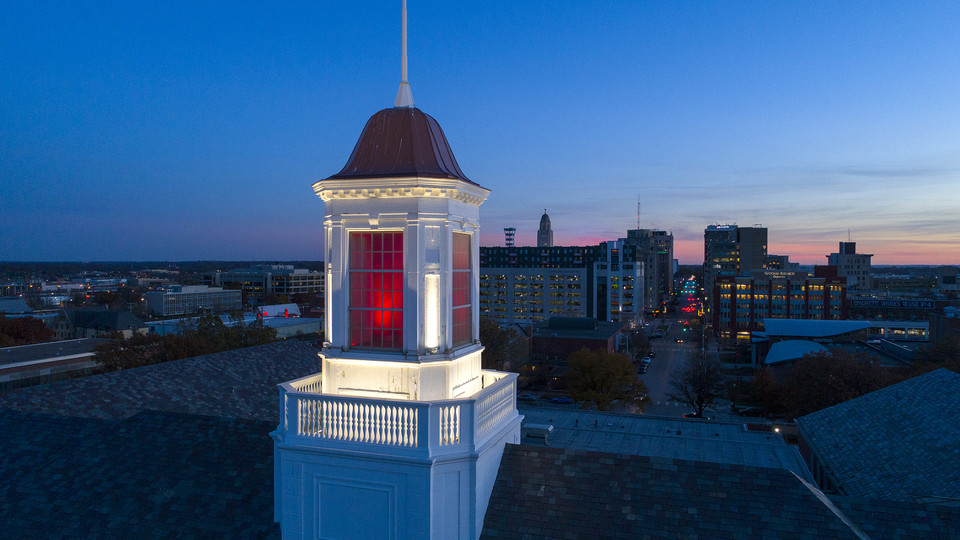 The sun sets as Nebraska's Love Library cupola glows over downtown Lincoln. Chancellor Ronnie Green announced Dec. 5 that the university will not be moving forward with additional proposed budget cuts.