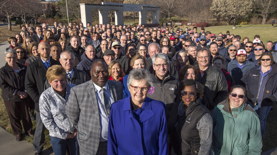 Christine Jackson (front, center, in blue coat) stands with more than 200 Business and Finance employees on the Nebraska Union Plaza. The employees showed up to surprise Jackson for the photo. She is retiring at the end of December after 17 years of service as Nebraska's vice chancellor for business and finance.