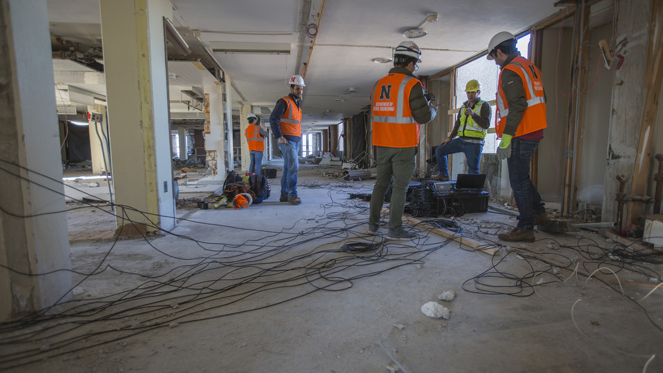 Nebraska's Richard Wood (in yellow) and members of his research team prepare to collect sensors and cables after completing a sensing survey of Pound Hall on Dec. 2. The research project is creating a complete picture of how dynamics of Cather and Pound halls are changing as demolition crews prepare the towers for a Dec. 22 implosion.