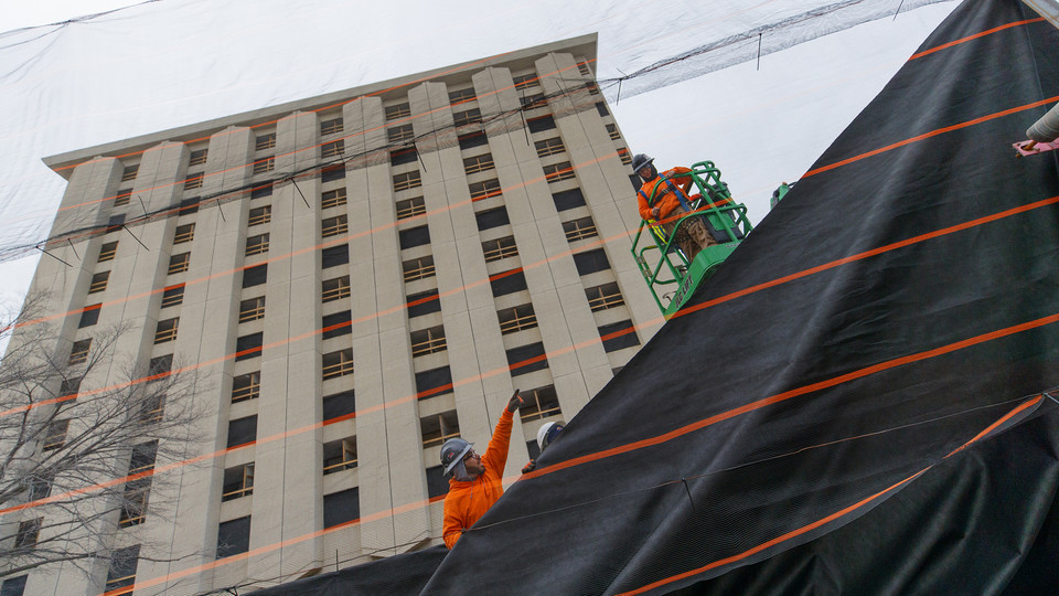 Ark Wrecking employees hang a protective fabric over a mesh wall along 17th Street on Aug. 21 as part of preparations for the razing of Cather and Pound halls. The wall is designed to keep dust and debris from reaching Knoll Residential Center and Cather Dining Center. The residence hall towers are scheduled to be imploded at 9 a.m. Dec. 22.