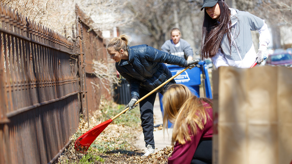 Huskers rake help rake leaves in a Lincoln neighborhood during the 2018 Big Event.