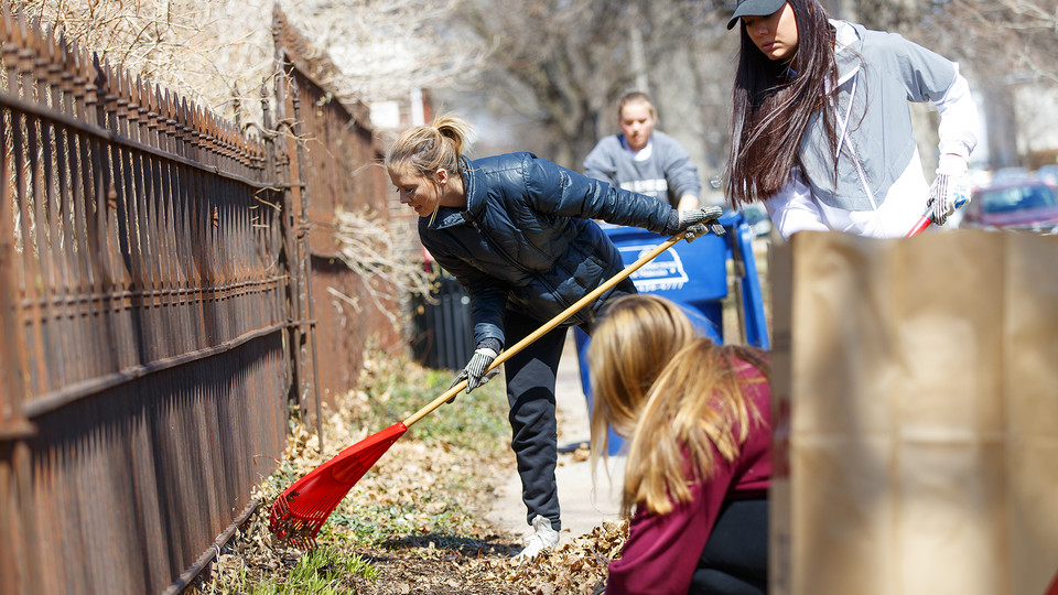Keeleigh Thayn (in blue jacket) and her Gamma Phi Beta sorority sisters rake leaves along P street during the Big Event on April 7. More than 3,000 students, faculty and staff participated in the day of service.
