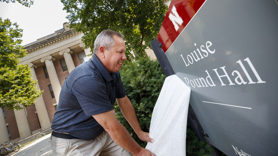 Bob McRoberts of SignsNow finishes applying the name to the newly renovated Pound Hall on Aug. 11. Named in honor of Louise Pound, the building was formerly known as the College of Business Administration and Social Sciences Hall. It is located at 12th and R streets.
