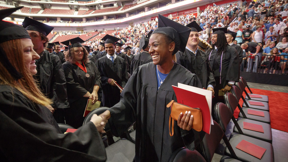 Kristen Dowell, a hurdler with Husker track and field and hospitality, restaurant and tourism management major, shakes hands with a fellow graduate during summer 2018 commencement exercises in Pinnacle Bank Arena.