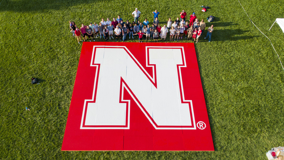 Volunteers pose with Nebraska's John Lang after breaking the Guinness World Record for largest mosaic built with tiny plastic bricks. This is the second world record set by Lang in as many years.