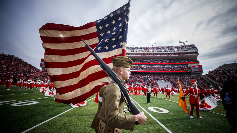 Dressed in World War I uniforms, ROTC students carry a flag into Memorial Stadium prior to the Nov. 10 football game with Illinois.