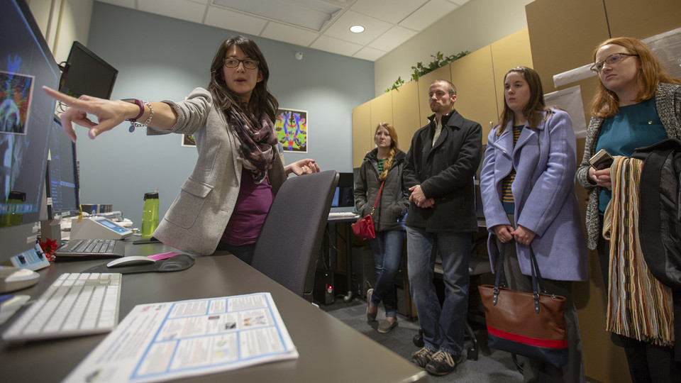 Maital Neta, assistant professor of psychology, demonstrates to legislative staff the MRI machine in Nebraska's Center for Brain, Biology and Behavior on Nov. 30.