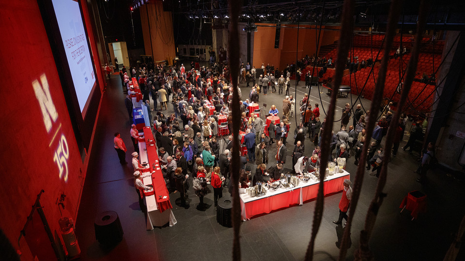 Students, faculty, staff, stakeholders and members of the public mingle on the Lied Center stage as part of a reception following the Jan. 15 State of the University address.