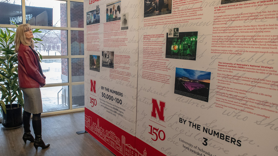 Nebraska's Diane Mendenhall reads about a key historic moment in the university's history as she looks at the N150 traveling exhibition in the Nebraska Union.