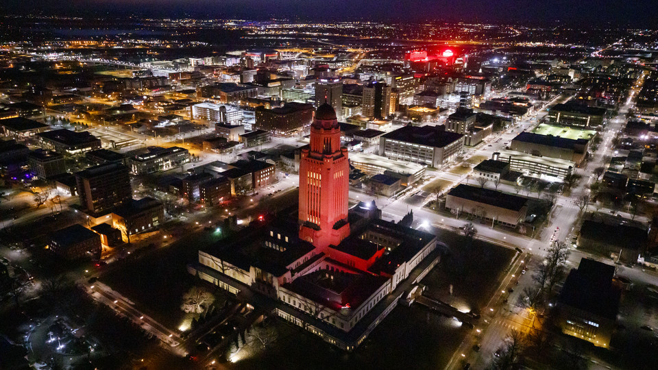 The Nebraska State Capitol shines red with Memorial Stadium and City Campus in the background.