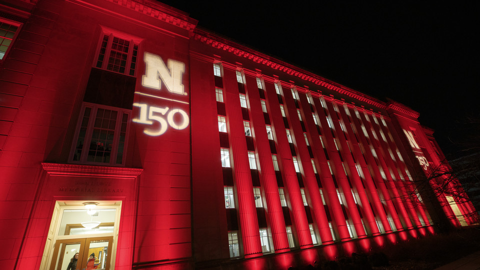 The architecture of Nebraska's Love Library is highlighted by red light and the N150 logo for Glow Big Red.
