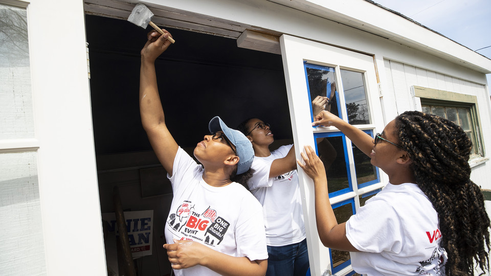 Nebraska's Iesha Bryant reaches for the top of the doorway as she and others in the Minority Pre-Health Association painted a shed and cleaned up a yard during the 2019 Big Event on April 6. More than 2,500 students, faculty and staff volunteered for the community service project.