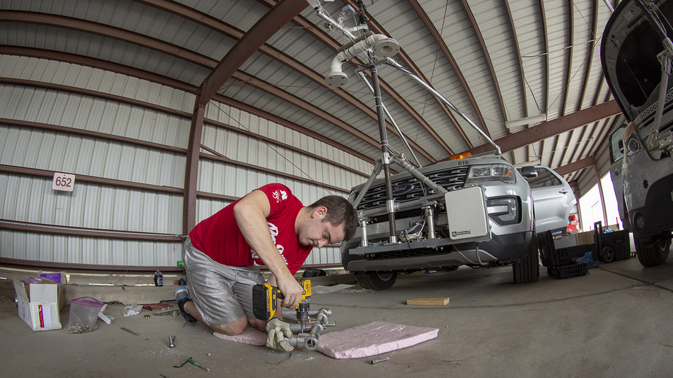 Graduate student Alex Erwin drills a pipe that will hold an instrument cluster on Nebraska's newest storm chase vehicle. Starting this spring, 13 Huskers will be part of TORUS, a national study designed to collect data about how severe storms and tornadoes are formed.