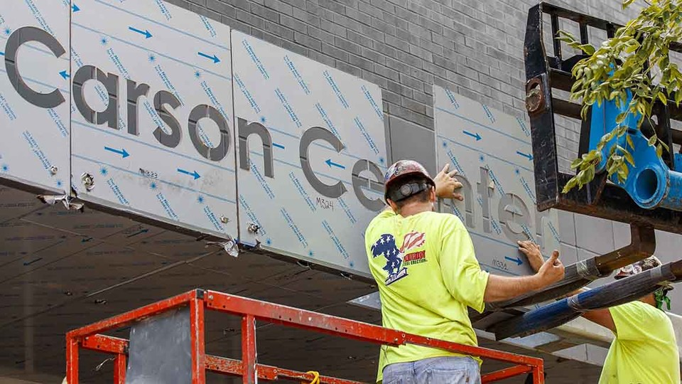 Contractors from Patriot Steel Erection install signage on the exterior of the new Carson Center for Emerging Media Arts on Aug. 5. The program launches with the start of the fall semester.