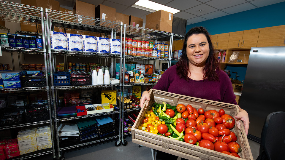 Morgan Smith, a graduate research assistant, shows a tote of fresh vegetables available at Husker Pantry. The pantry and Money Management Center have moved from the Nebraska Union to the University Health Center.