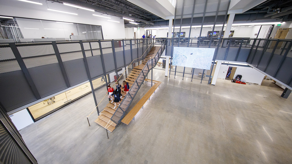 A group of students walk down the stairs in the atrium of the new Johnny Carson Center for Emerging Media Arts. The open area will feature moveable walls to create flexible spaces once all the furniture arrives.