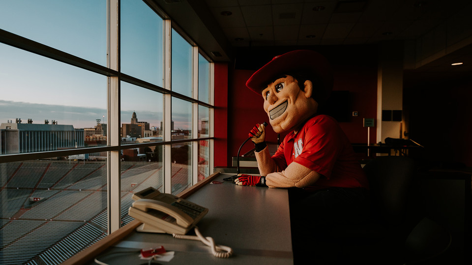 Herbie Husker practices his play-by-play skills in the Memorial Stadium press box. Herbie will be honored during the Sept. 17 Celebration of Service for his 45th years as the university mascot.