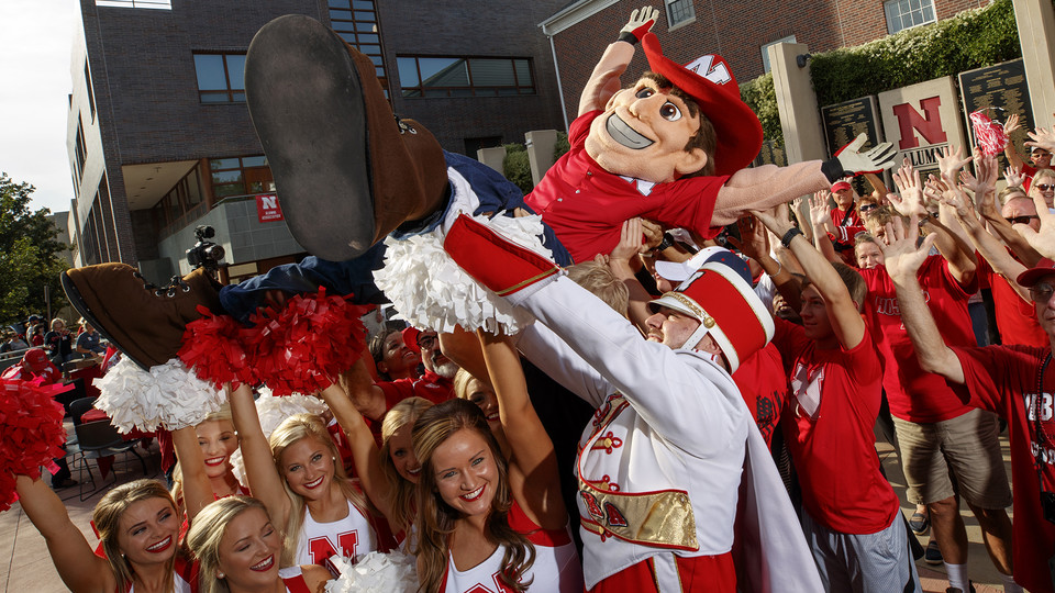 Herbie Husker crowd surfs with some help from the Cornhusker Marching Band, cheerleaders and Nebraska alumni outside the Wick Alumni Center.