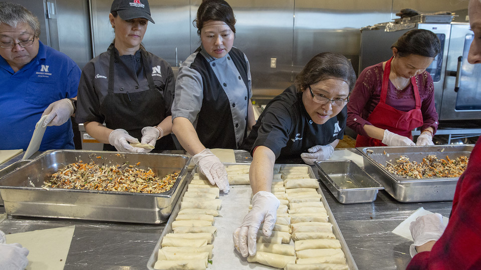 "Thom ""Emily"" Tran (third from left) and Amy Tran (fourth from left) adjust raw egg rolls on a baking sheet in the Cather Dining Center on Jan. 9. For the second year, Cather Dining Center is offering handmade vegetarian egg rolls based on a recipe provided by Tran. The homemade option has proven popular with students and is healthier and cheaper than purchasing a frozen option."