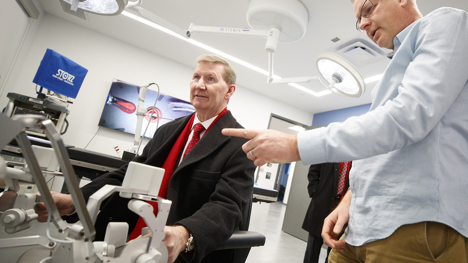 Shane Farritor (right), professor of mechanical and materials engineering, helps Ted Carter control a surgical robot in a Virtual Incision lab at Nebraska Innovation Campus. Carter's two-day tour included stops at City, East and Nebraska Innovation campuses.