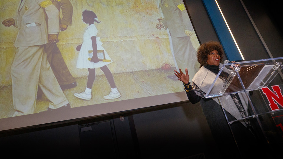 "With Norman Rockwell's ""The Problem We All Live With"" in the background, civil rights icon Ruby Bridges delivers the MLK Week address on Jan. 22 in the Willa Cather Dining Center's Red Cloud Room. More than 275 attended the event. The painting depicts Bridges as she is led by U.S. Marshals into an all-white New Orleans school."