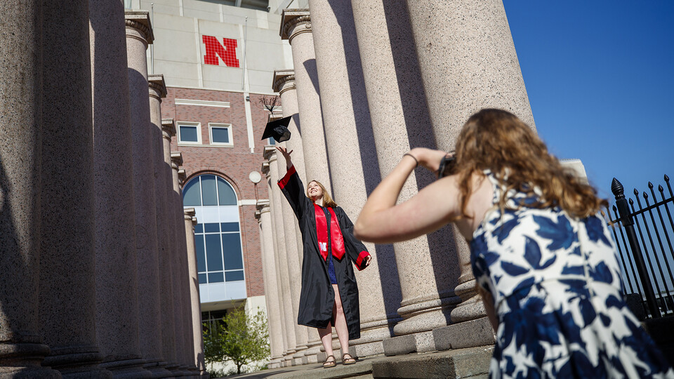 Rose Wehrman (in regalia) and Sarah Schilling prepared for commencement in spring 2020 by shooting photos amongst the Columns by Memorial Stadium. The iconic pillars, which have stood by Memorial Stadium for 86 years, will be on the move this summer as construction begins on the Huskers' new athletics facility.