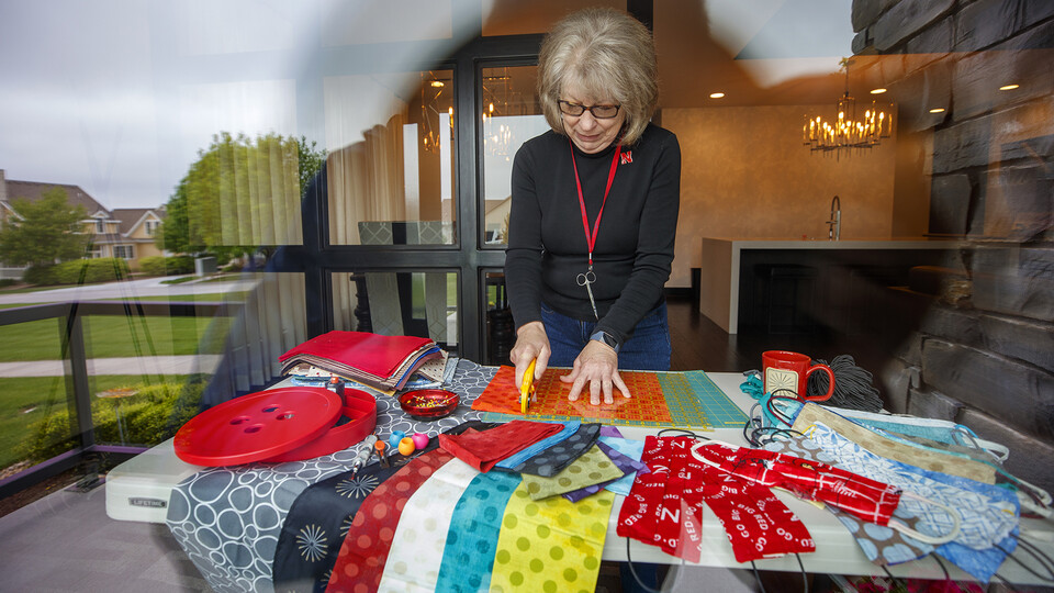 Joy Shalla Glenn, a public programs and membership assistant with the International Quilt Museum, cuts fabric for masks in her living room. She is among the more than 70 individuals who answered the museum's request to sew cloth face coverings for university employees.