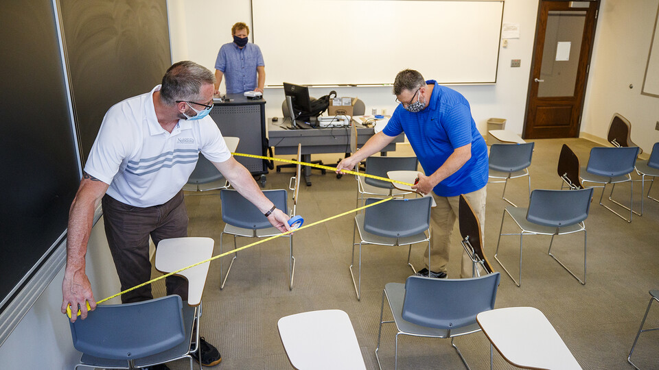Jack Dohrman (left) and and Shawn Languis (right), use tape measures to gauge physical distancing needs within an Avery Hall classroom. Keith Derickson, a support manager with academic technologies, stands in the instructor position to assist with the mapping. Based on their measurements, seating in this classroom will shift from 35 desks in a regular semester to 14 in the fall. The change allows the university meet the six-foot social distancing needs related to COVID-19. In large lecture halls, seating capacity is expected to be reduced to 20 percent.