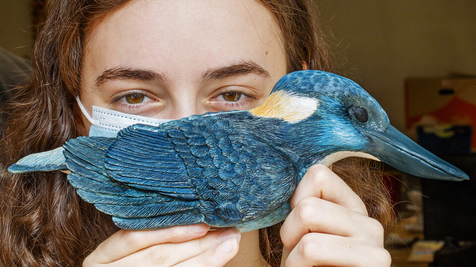 Kinga Aletto, a junior in College of Agricultural Sciences and Natural Resources, holds her life-sized clay model of the Javan blue-banded kingfisher. Creating the model of the critically-endangered bird is part of her UCARE research project.