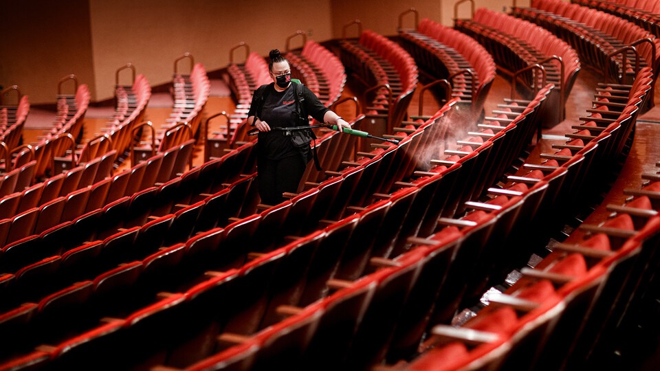 Jillian Stewart, assistant custodial services manager for the Lied Center for Performing Arts, disinfects seats after classes finished on Sept. 23. The Lied — which is among the first performing arts venues to reopen after national shutdowns in the spring — is using a multi-layered approach to protect against the spread of COVID-19. It is also hosting university classes in the day and performances in the evening.