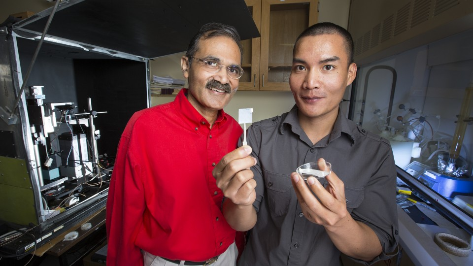 Ravi Saraf (left) and fellow researcher Chieu Van Nguyen, who is holding up a thin membrane on a slide cover.