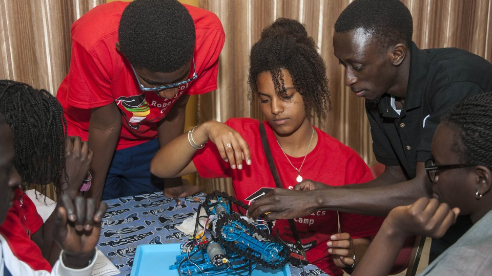 Sidy Ndao (righ) offers advice to a student team as it finishes assembling a robot at the SenEcole robotics camp in Dakar, Sengal, in March.