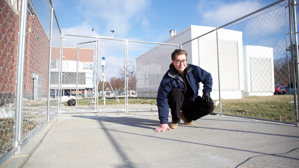 Chris Tuan, professor of civil engineering at the University of Nebraska-Lincoln, stands on a slab of conductive concrete that can carry enough electrical current to melt ice during winter storms. Tuan is working with the Federal Aviation Administration and U.S. Strategic Command on multiple applications for his patented concrete mixture.