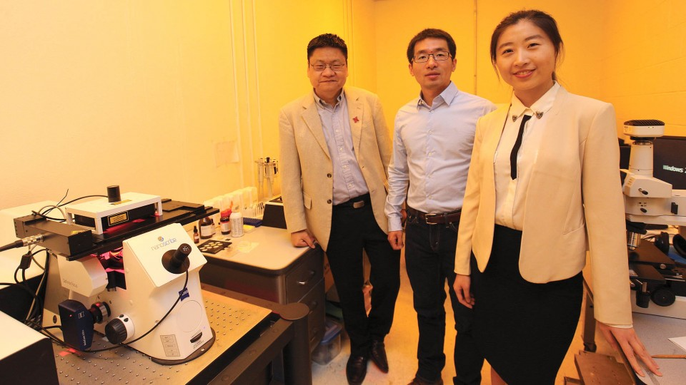 UNL engineers (from left) Yongfeng Lu, Lijia Jiang and Ying Liu stand in a laboratory illuminated by a special light designed to protect the microscope at left.