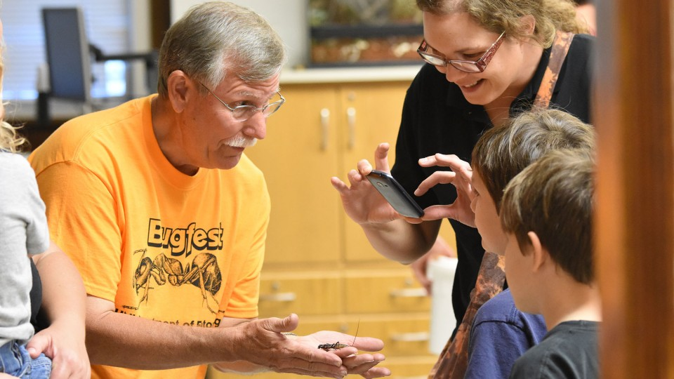 Entomology Professor Fred Baxendale introduces Vinnie the vinegaroon to a BugFest guest in 2015.