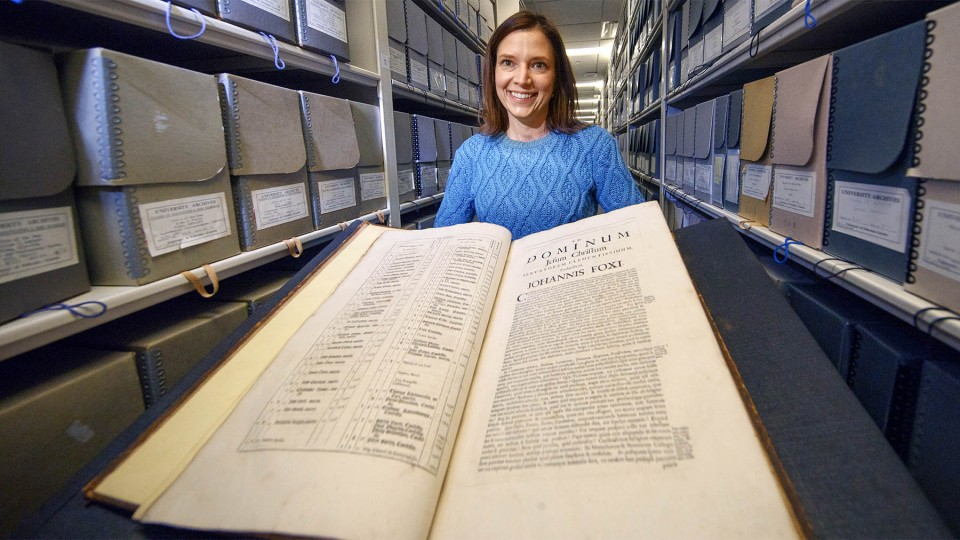 "Traci Robison, photo and exhibits specialist with Archives and Special Collections in University Libraries, displays a volume of John Foxe's ""Book of Martyrs."""