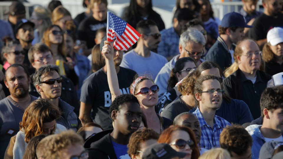 Woman holding an American flag during a 2016 presidential election rally